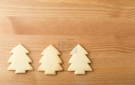 Christmas tree cookies over the wooden background