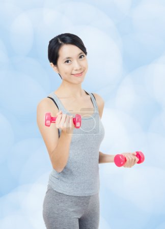 Asian woman lifting dumbbell