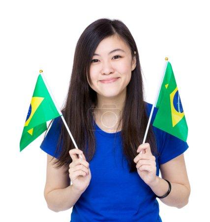 Asian woman holding Brazil flags