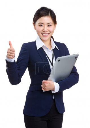Young businesswoman holding laptop with thumb up