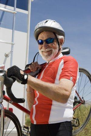 Photo pour Portrait d'un homme âgé portant un vélo sur son épaule - image libre de droit