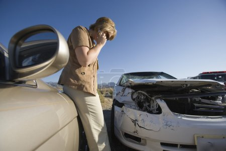 Young woman using mobile phone by car wreckage