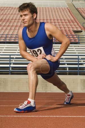 Photo for Male athlete warming up before starting race - Royalty Free Image