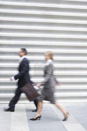 Photo pour Vue latérale d'un homme d'affaires et d'une femme flous marchant rapidement - image libre de droit