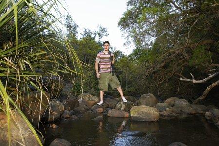 Photo pour Adolescent garçon debout sur pierre par rivière - image libre de droit