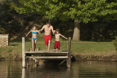 children with father jumping into lake