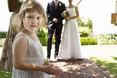 Cute Girl Holding Flower At Wedding