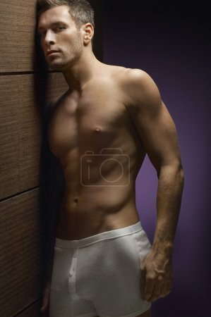 Shirtless Man Leaning By Wooden Wall