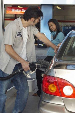 Photo pour Femme regardant la station-service pomper de l'essence dans la voiture - image libre de droit