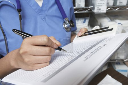 Doctor Writing In Patient's Medical Chart