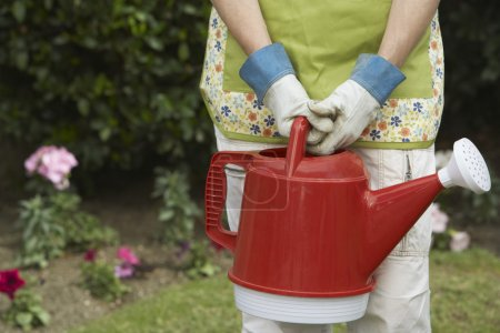 Woman carrying watering can