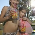Portrait of little girls in swimwear drinking juic...