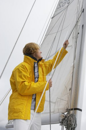 Photo for Young Caucasian man holding rigging on sailboat - Royalty Free Image