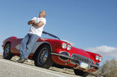 Happy Man Standing beside Classic Car On Road