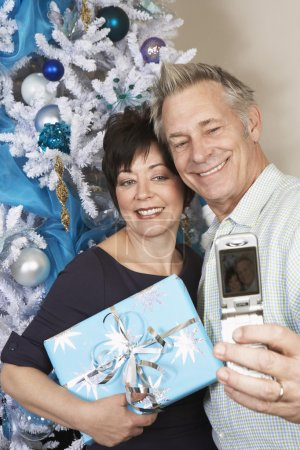 Couple Taking Self Portrait With Cell Phone In Front Of Christmas Tree