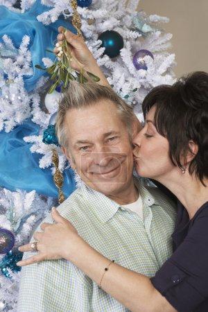 Woman Kissing Senior Man Under Mistletoe