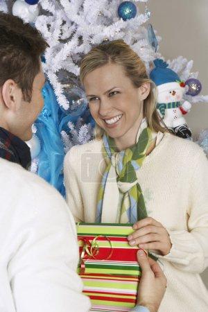 Photo pour Heureuse femme recevant un cadeau d'un homme devant un arbre de Noël - image libre de droit
