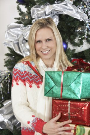 Photo for Portrait of a young Caucasian woman carrying stack of gifts against decorated Christmas tree - Royalty Free Image