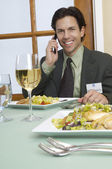 Businessman On A Call At Dining Table