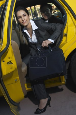 Female Executive Getting Out Of Taxi