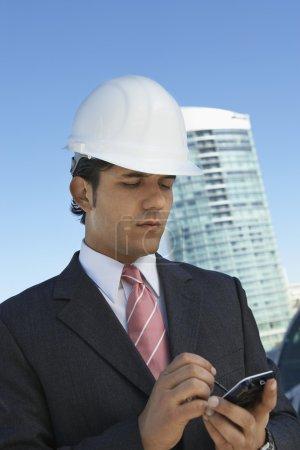 Businessman In Hardhat Using PDA