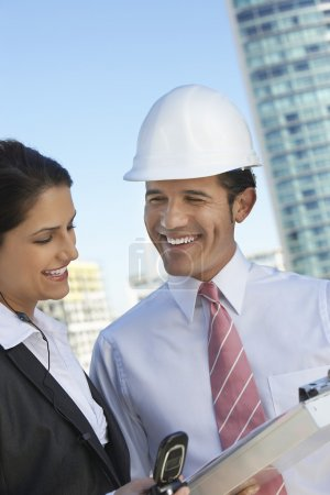 Businessman Showing Clipboard To Businesswoman