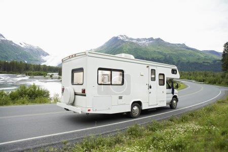 Photo pour Véhicule récréatif passant par une route au bord du lac avec montagne en arrière-plan, Alaska, États-Unis - image libre de droit