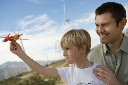 Boy Holding Toy Glider With Father