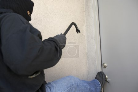 Photo for Burglar with crowbar kicking the door of house - Royalty Free Image