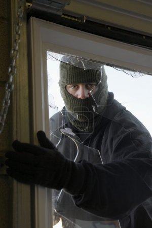 Masked Thief Breaking In Through Window