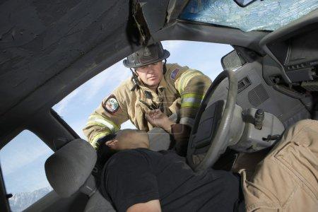 Photo pour Pompier secourant victime d'un accident de voiture - image libre de droit