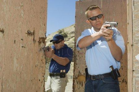 Photo pour Deux officiers pointant des armes de poing au champ de tir pendant l'entraînement aux armes - image libre de droit