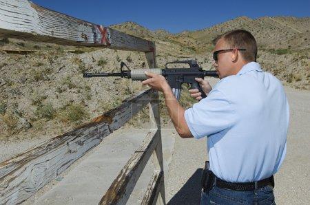 Man Aiming Rifle At Firing Range