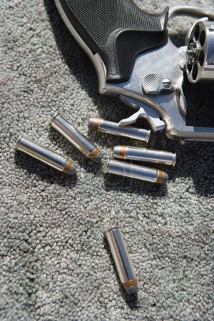 Photo for Closeup of hand gun and bullets on grey carpet - Royalty Free Image