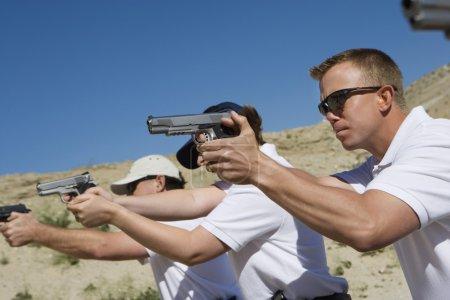 Photo pour Viser des armes de poing au champ de tir pendant l'entraînement aux armes - image libre de droit