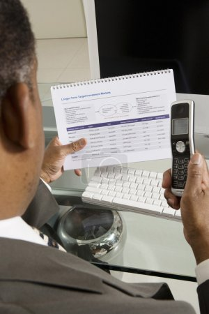 Businessman With Investment Form And Cell Phone