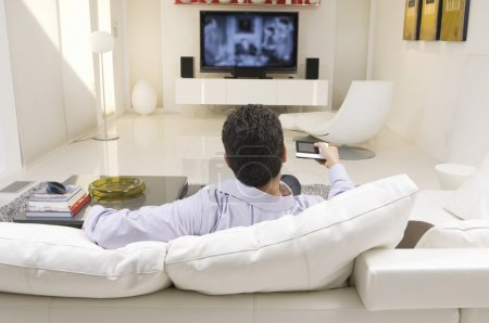 Photo for Rear view of a man watching television in living room - Royalty Free Image