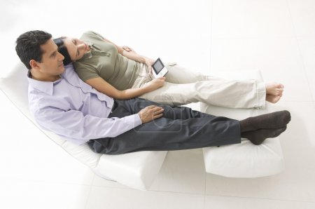 Photo for Full length of a loving couple with remote control relaxing on chair - Royalty Free Image