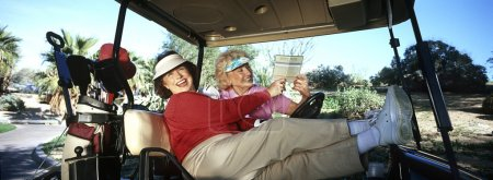 Photo for Two women laughing in golf cart with scorecard - Royalty Free Image