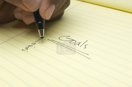Hand Writing List Of goals On Notepad