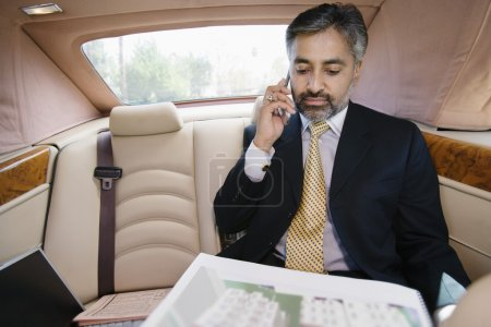 Businessman Looking At Notepad While On Call In Car