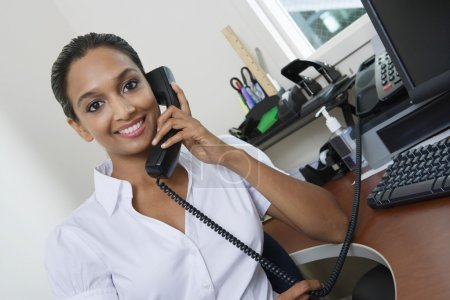 Businesswoman Communicating On Landline Phone