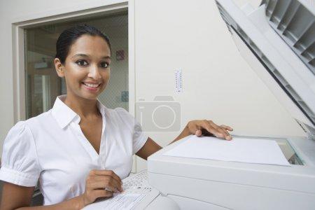 Happy Businesswoman Using Fax Machine In Office