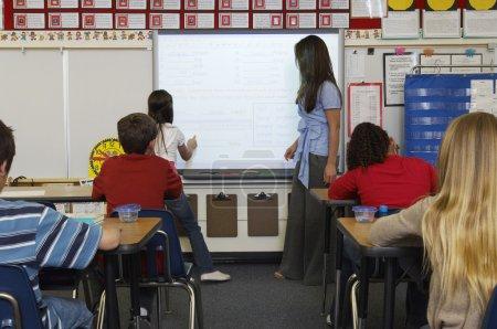 Photo pour Enseignante debout près du tableau blanc et aidant écolière dans la classe - image libre de droit