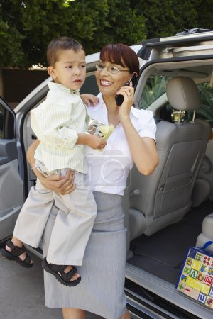 Businesswoman Carrying Son While On Call