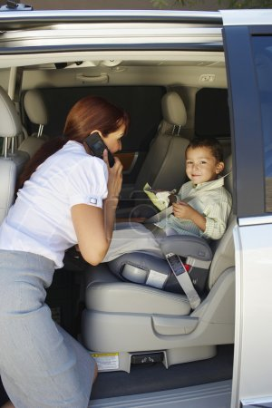 Business Woman Using Mobile Phone With Son In Car