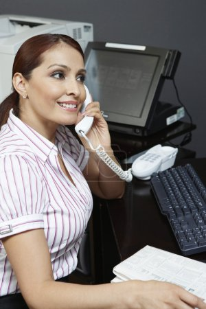 Businesswoman Using Phone In Office