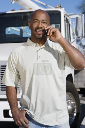 Truck Driver On Phone In Front Of A Truck