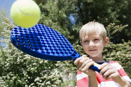 Boy Playing With Paddle And Ball