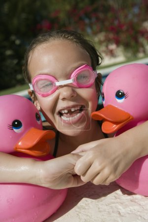 happy girl with plastic ducks in pool